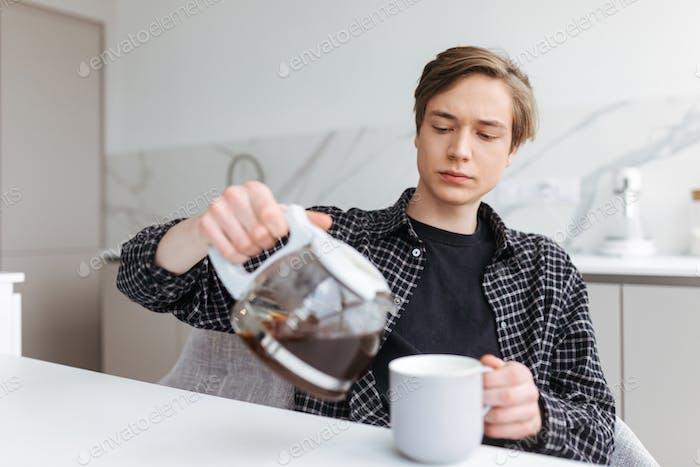 Junger Mann sitzt und gießt Kaffee in der Küche zu Hause