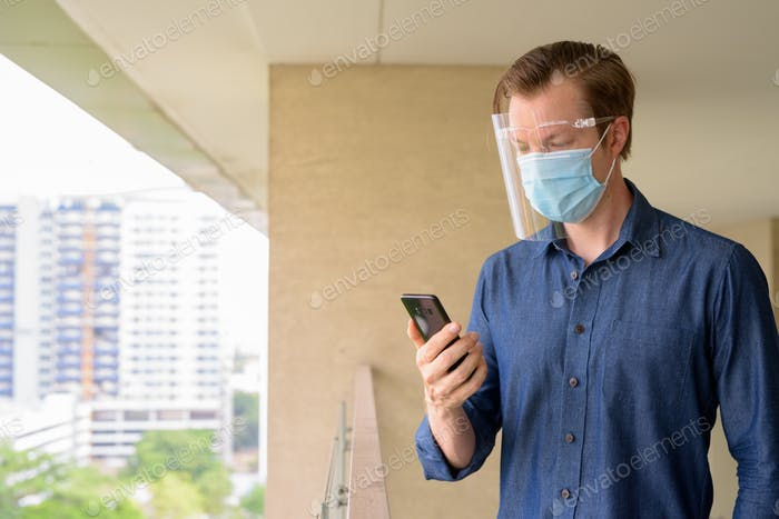 Young man with mask and face shield using phone against view of the city