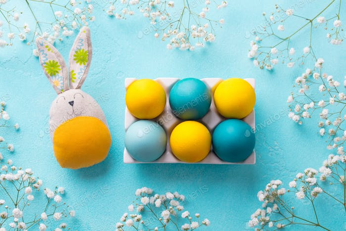 Easter colorful eggs with a bunny and white flowers. Blue background. Top view.