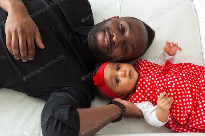 Young african american father holding with her baby girl
