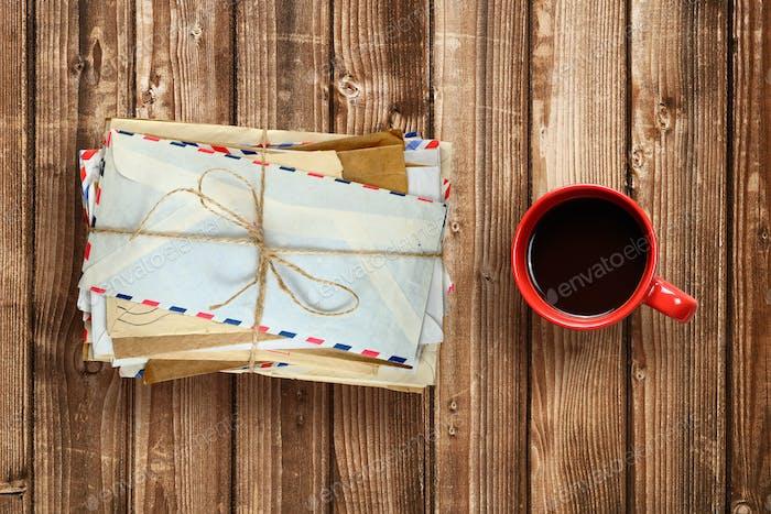 Stapel von alten Umschlägen und Kaffeetasse auf Holztisch-Ansicht