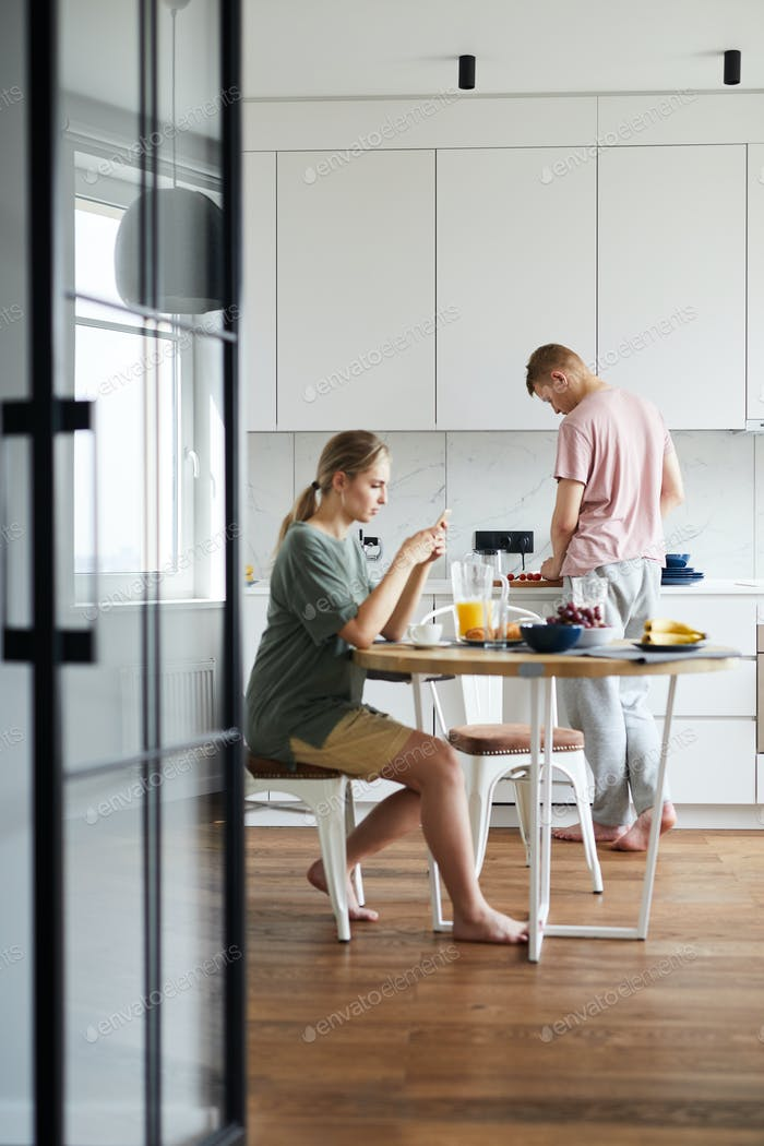 Young woman having breakfast and using smartphone while her husband cooking