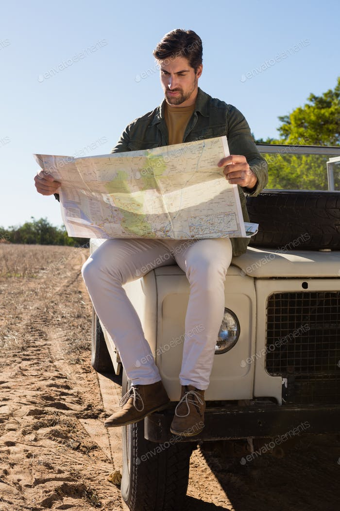 Full length of man reading map while sitting on off road vehicle