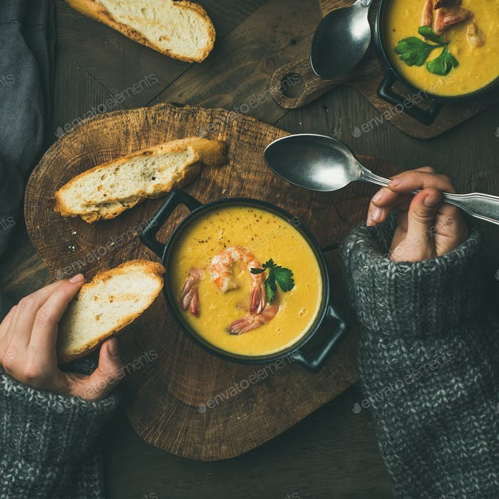Woman in sweater eating corn soup with shrimps, square crop