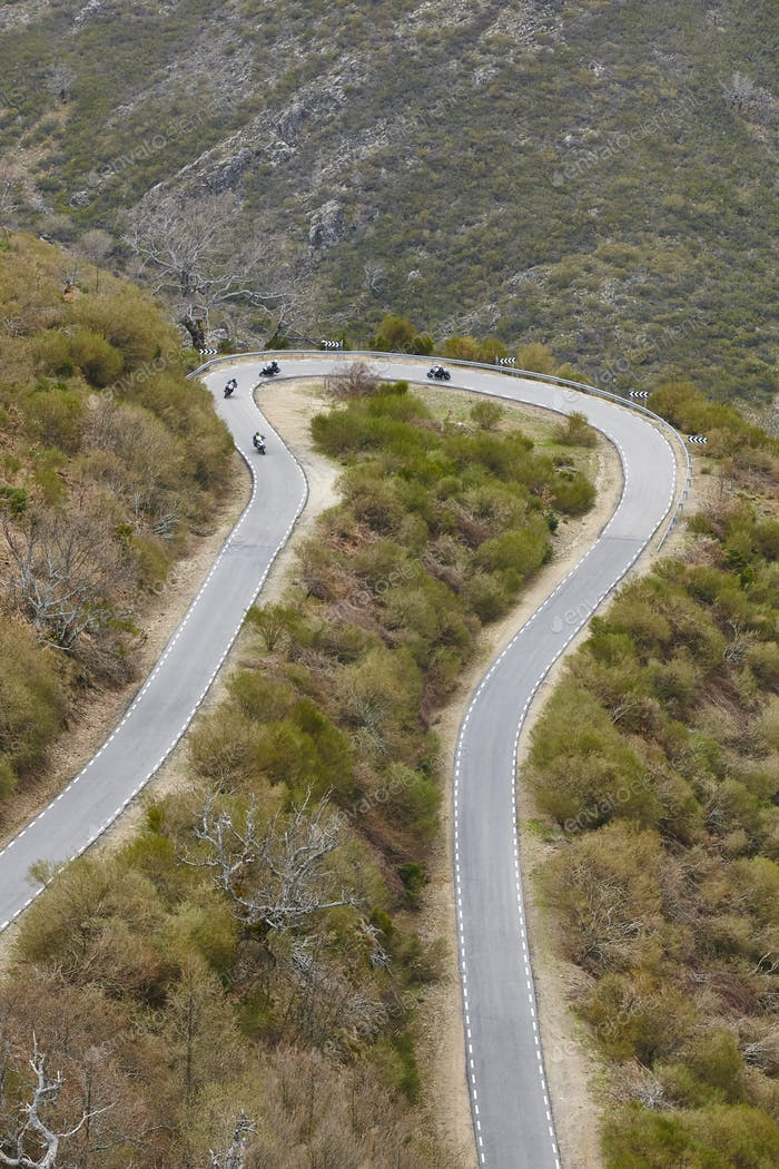 Curved asphalt mountain road with motorcycles. Rural scenic travel. Vertical
