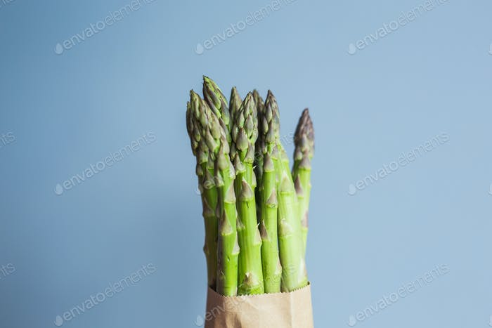 Bundle of green asparagus on blue background. Concept of vegans, vegetarians and healthy food