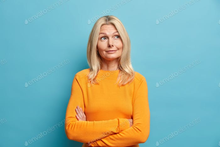 Middle aged woman keeps arms folded and thinks deeply about something has wrinkled skin dressed in c