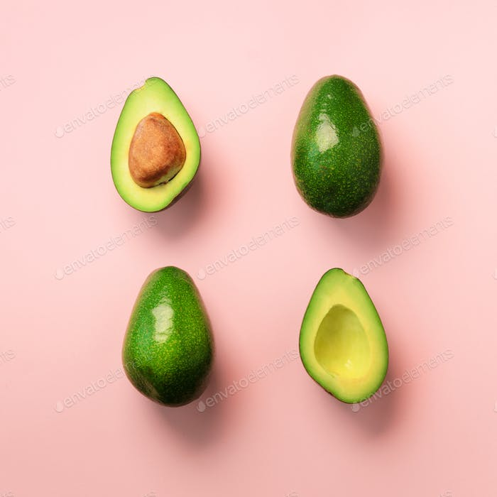 Organic avocado with seed, avocado halves and whole fruits on pink background. Top view. Square crop