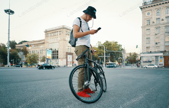 Young stylish man texting on the phone while standing aside bike