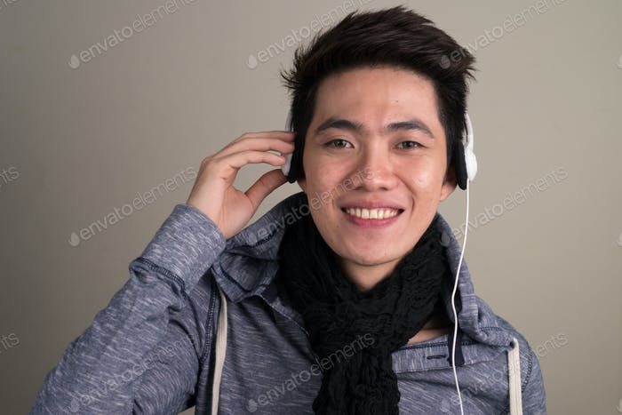 Portrait of young handsome Asian tourist man