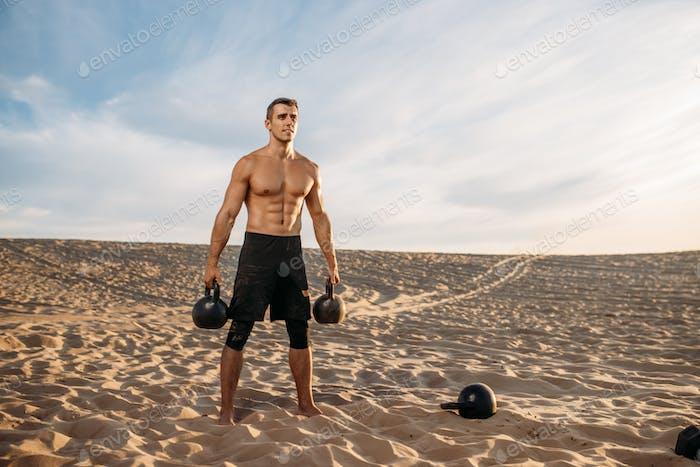 Männlicher Athlet mit zwei Kettlebells in der Wüste