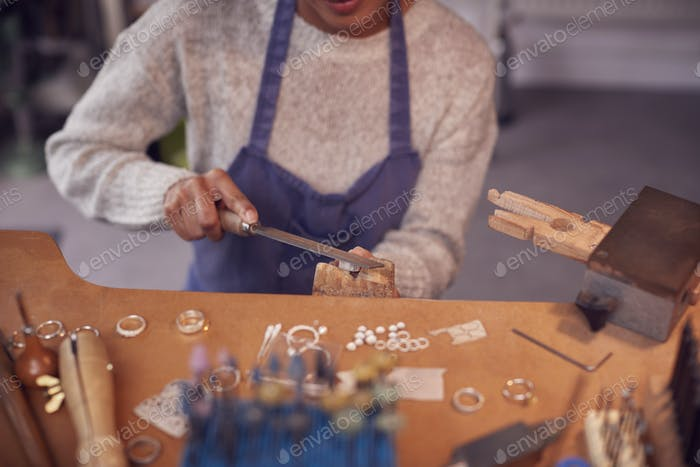 Close Up Of Female Jeweller Working On Ring With File In Studio