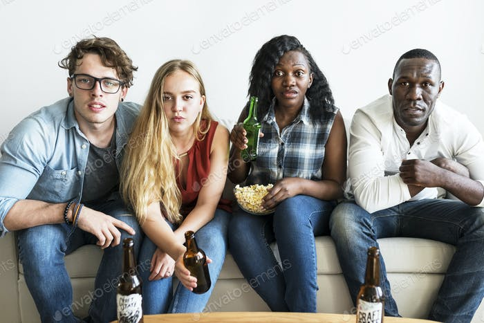 Group of diverse friends watching sports together seriously