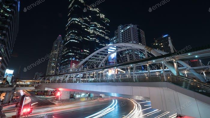 Straße und Fußgängerüberführung in der Nacht Bangkok