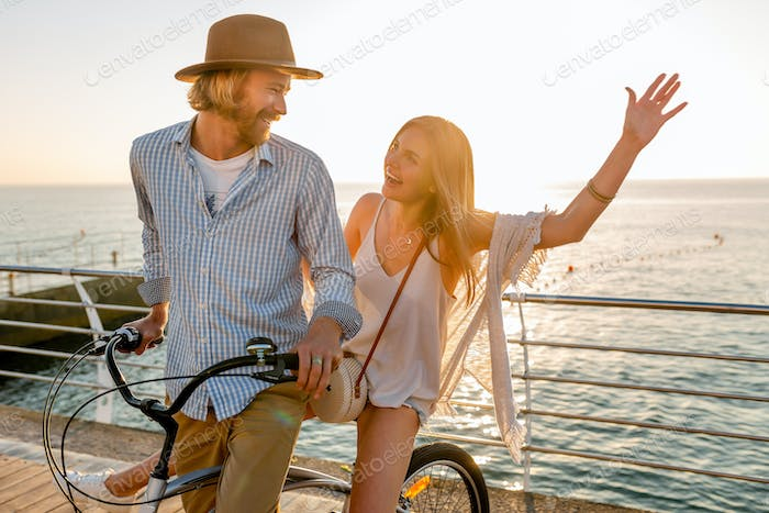 attractive happy couple traveling in summer on bicycles