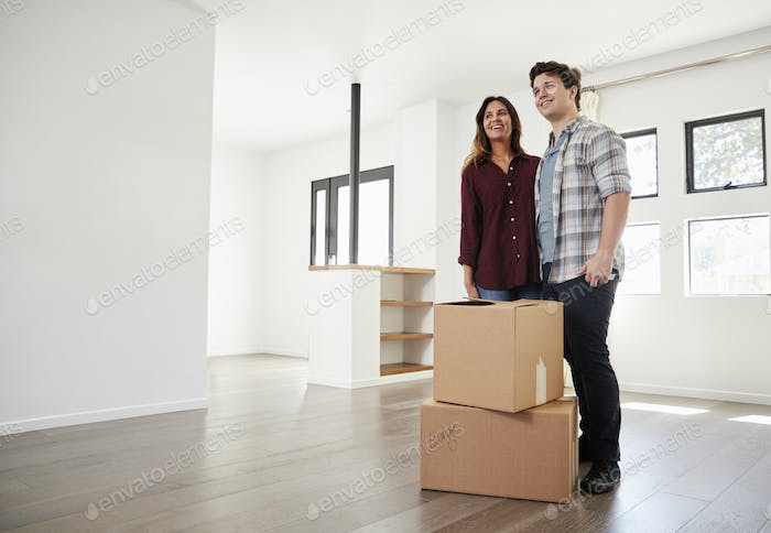 Excited Couple Standing With Boxes In New Home On Moving Day