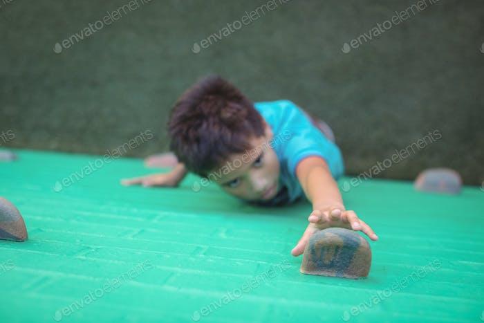 Boy reaching climbing holds on wall