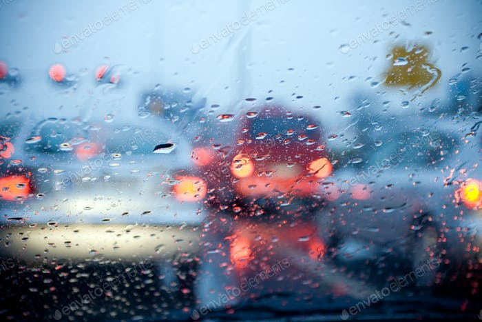 Car driving in a rain storm with blurred red lights