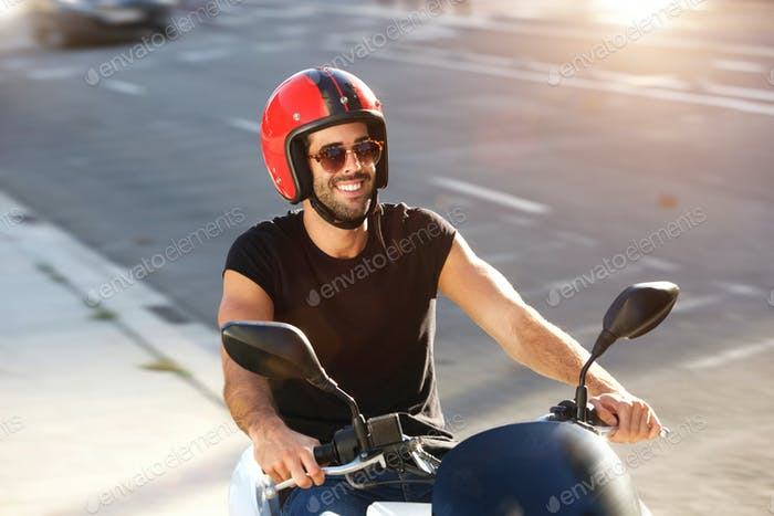 Portrait of happy man with helmet and sunglasses on motorcycle ride