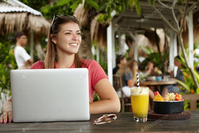 Schöne junge Frau Freiberuflerin lässig gekleidet mit generischem Laptop für Remote-Arbeit, hav