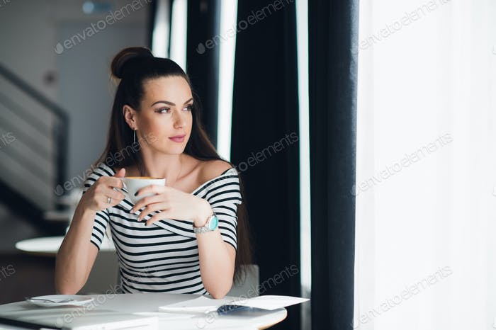 Attractive adult woman is sitting in a cafe and gazing through a window dreaming of someone, while