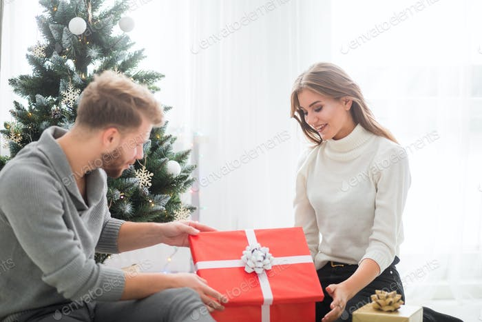 Cheerful couple in love opening Christmas gifts together on floor next to Xmas tree