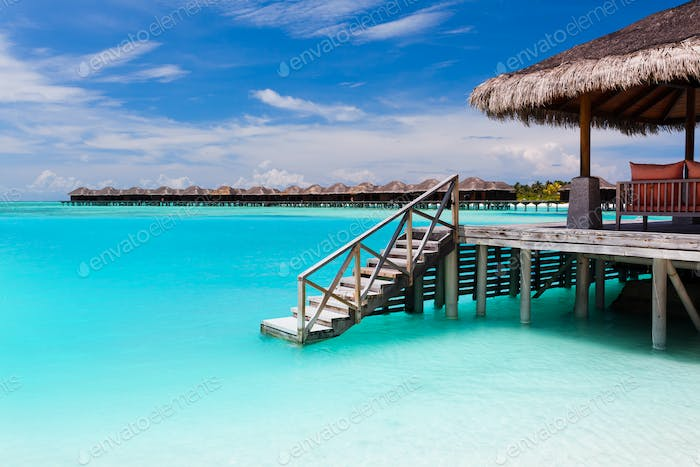 Over water bungalow with steps into blue lagoon