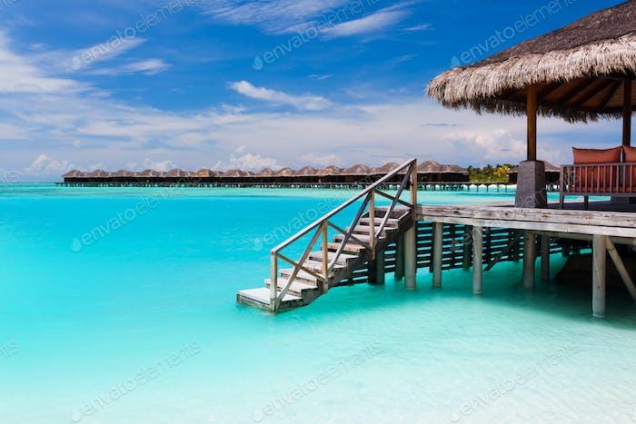 Bungalow über Wasser mit Stufen in die blaue Lagune