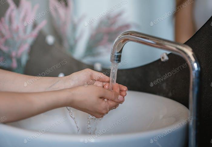 Unerkennbare junge Frau Waschen Hände in Waschbecken im Bad, Nahaufnahme der Hände