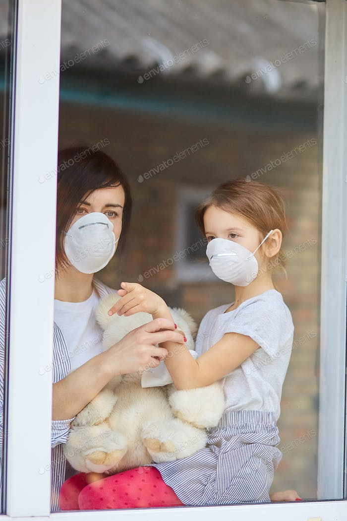 Mother with daughter child in mask looking from window, coronavirus.