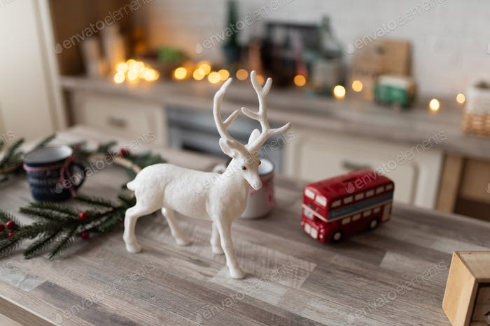 A decorative deer stands on a table in a Scandinavian kitchen.