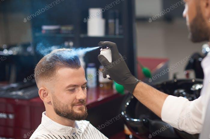 Friseur Fixierhaare von männlichen mit Spray im Friseurladen