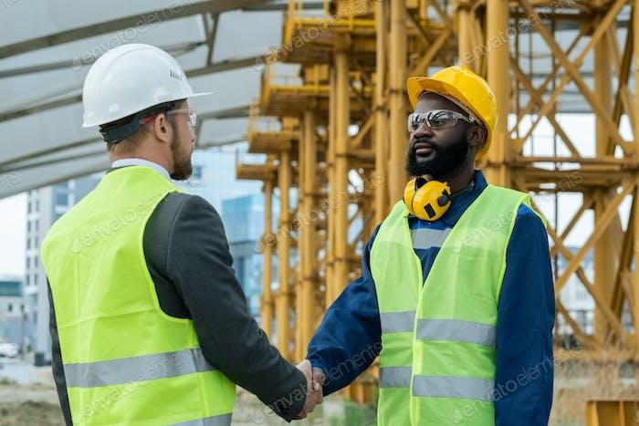 Engineers shaking hands outdoors