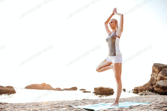 Junge Frau stehend in Yoga-Pose auf einem Bein