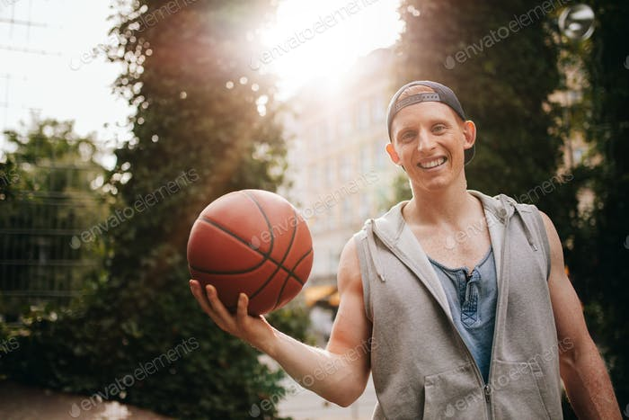 Smiling young man holding a basketball on court
