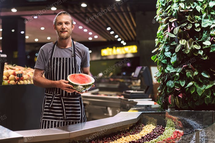 Young salesman in striped apron behind counter joyfully looking