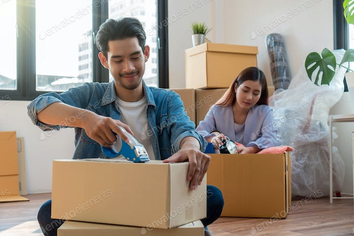 Asian young couple packing big cardboard box for moving in new home, Moving and House Hunting