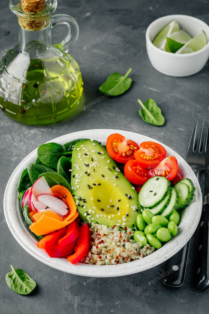 Buddha bowl. Avocado, quinoa, tomatoes, cucumbers, radishes, spinach, carrots, paprika and edamame.