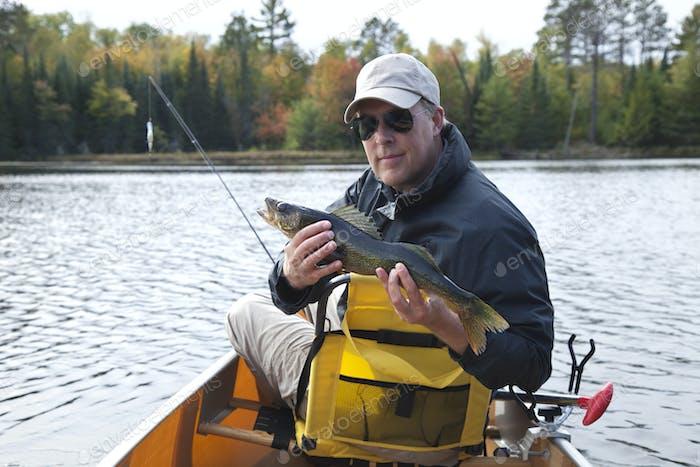 Glücklicher Fischer hält eine Zander auf einem nördlichen Minnesota See