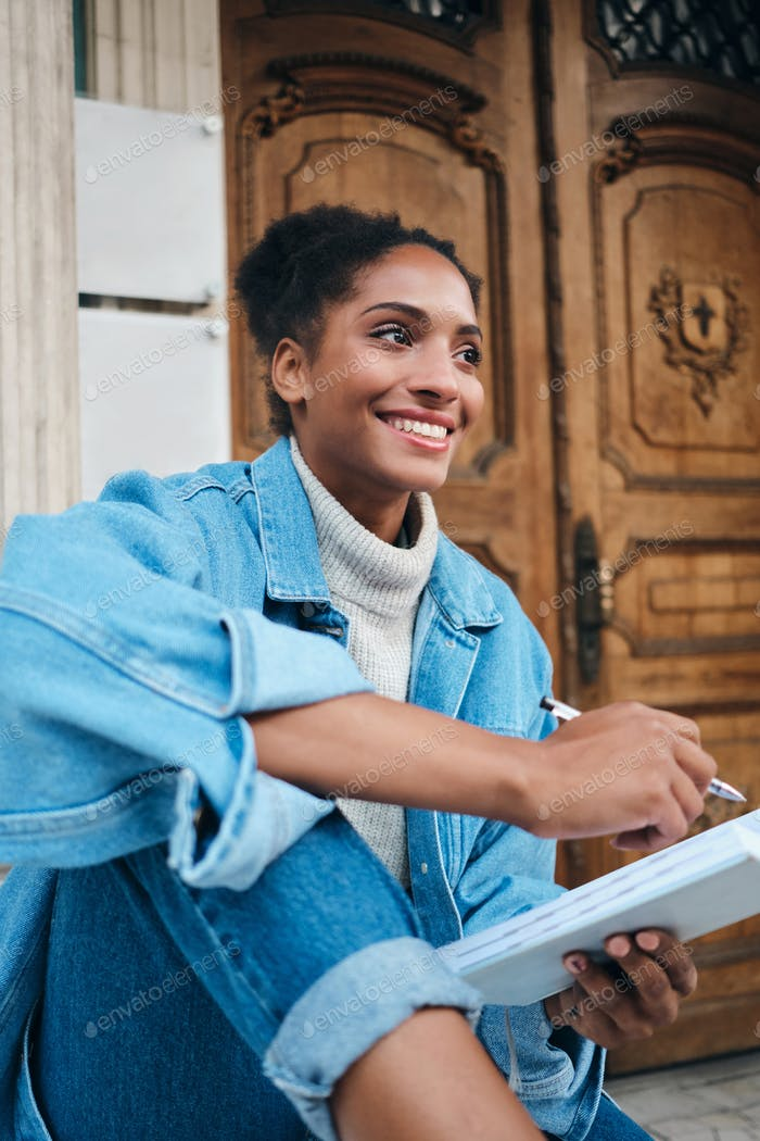 Cheerful African American student girl in denim jacket with notebook joyfully studying outdoor