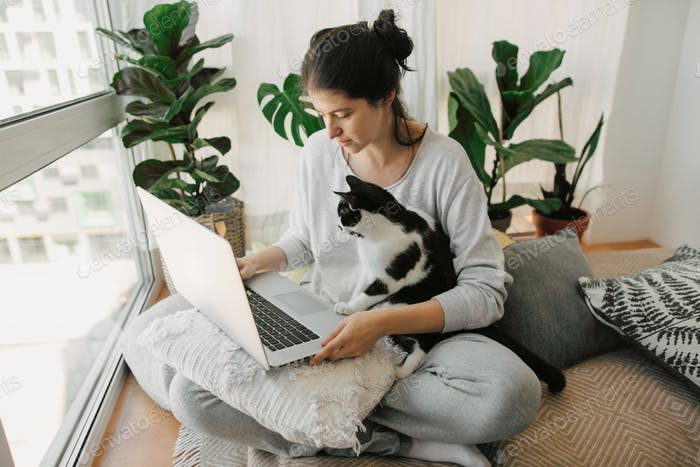 Casual girl working on laptop with her cat, sitting together in modern room with pillows and plants