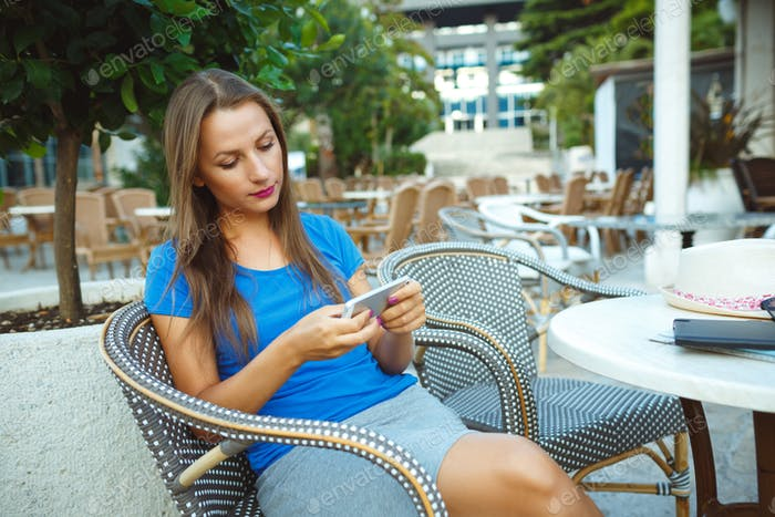 Young woman relaxing in the outdoor cafe and using smartphone
