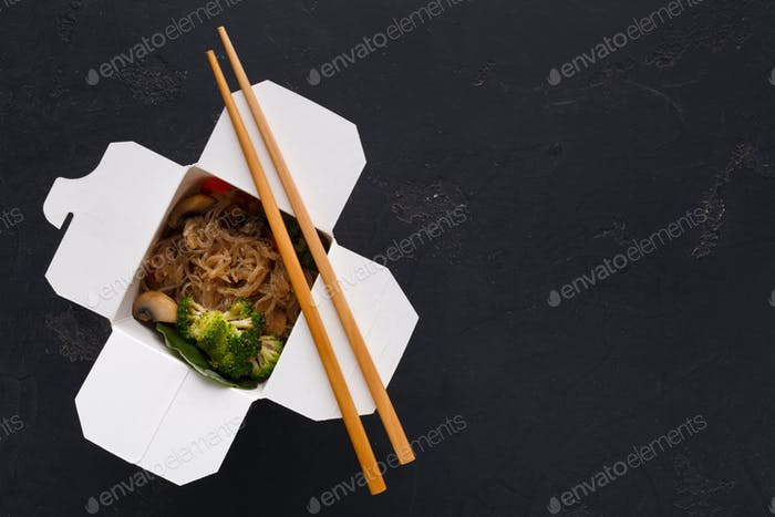 Asian food in delivery box on black background