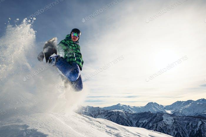 сноубордист едет и прыгает с снежного холма