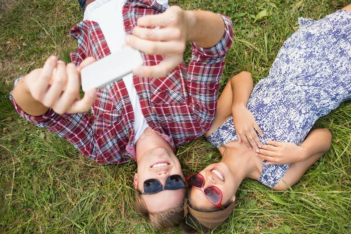 Couple relaxing in the park taking selfie on a sunny day