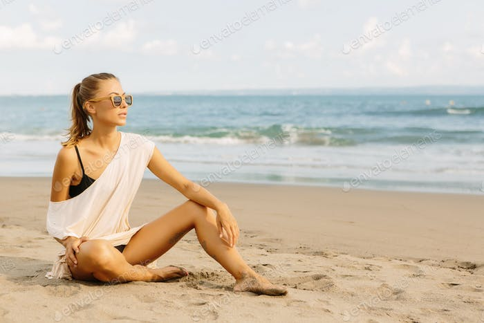 Pretty woman sit on the seashore.