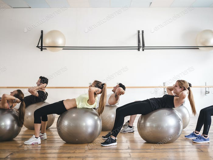 young people doing a yoga lesson with a gym ball