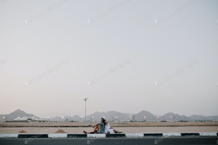 Portrait of two travelers resting on the road, waiting for a ride and enjoys beautiful landscape. Yo
