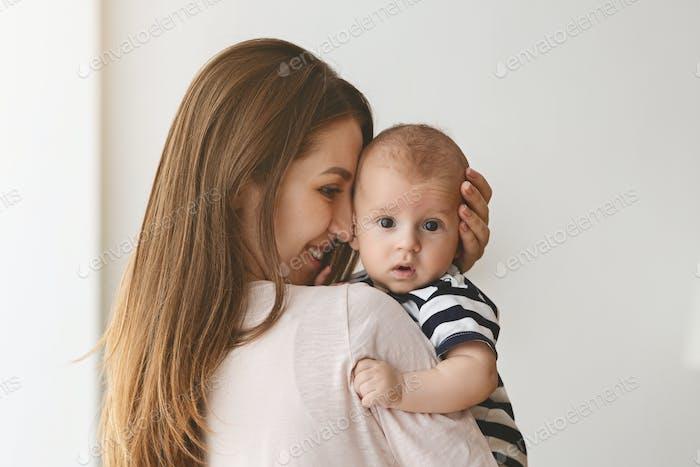 Porträt von schönen jungen Mama umarmen ihr kleines neugeborenes Sohn