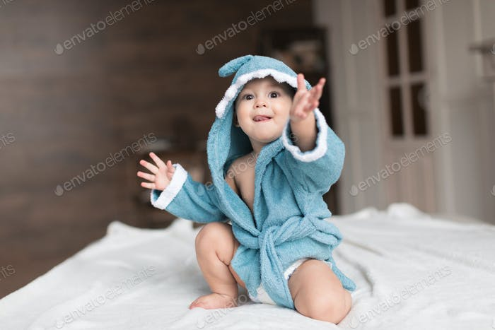 Happy baby boy in blue robe posing on bed